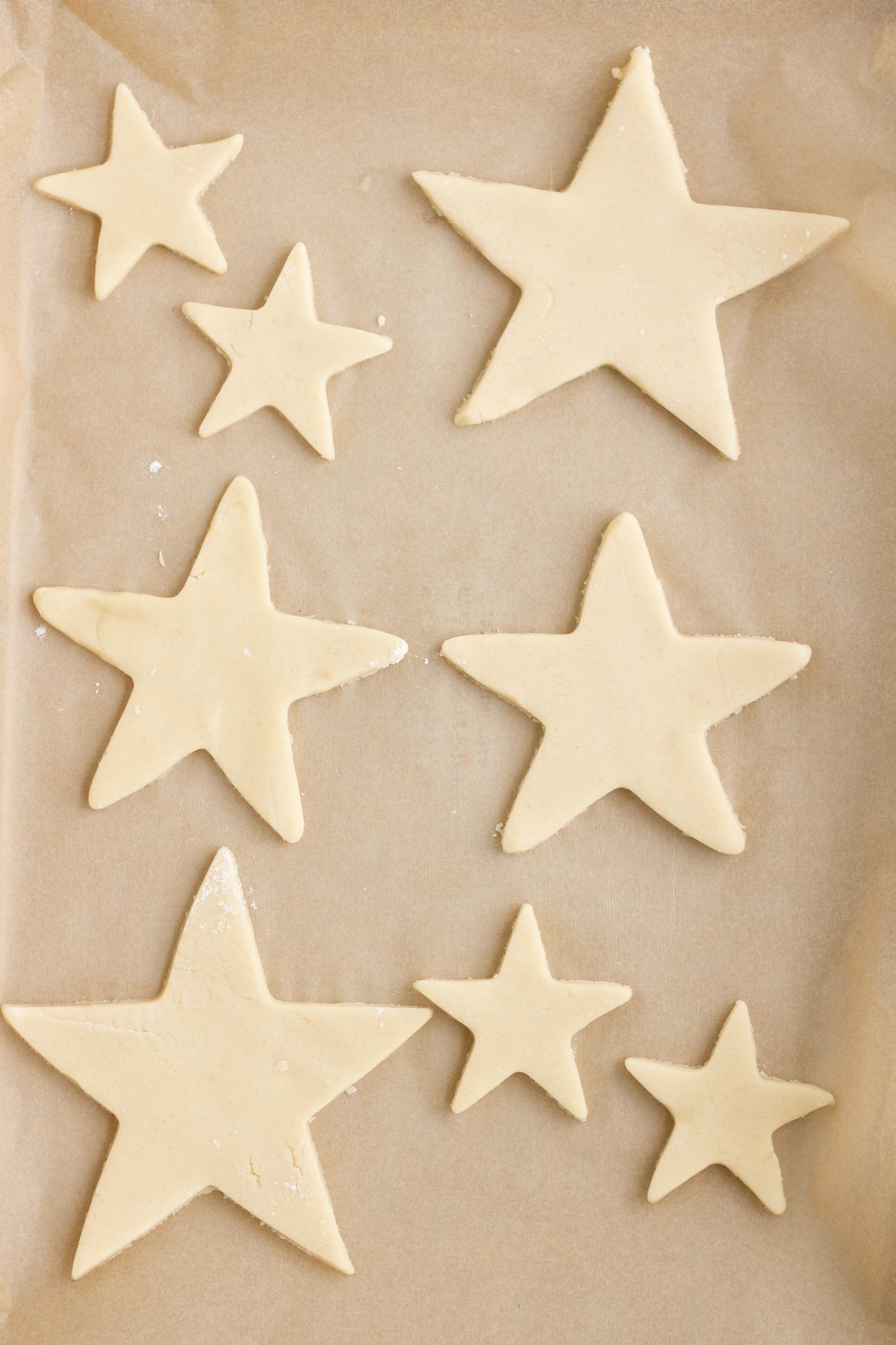 Cut out sugar cookies in a star shape on a parchment lined baking sheet.