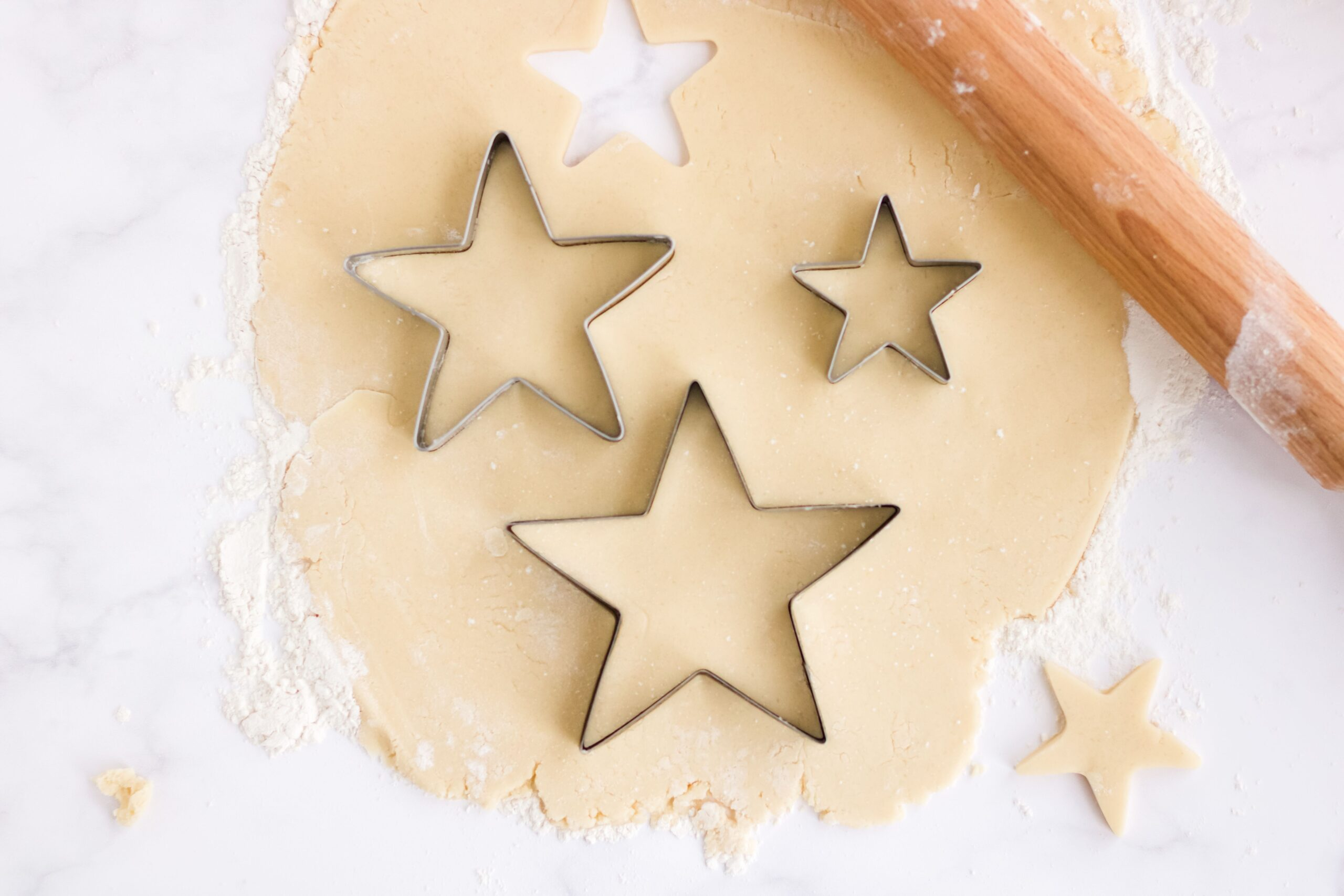 Sugar cookie dough and a rolling pin with star shaped sugar cookies making cut outs.