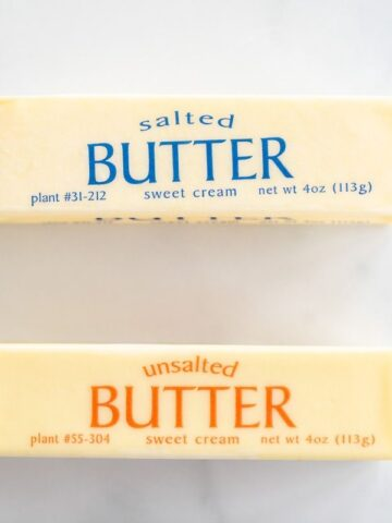 A stick of unsalted butter next to a stick of salted butter on a marble surface.