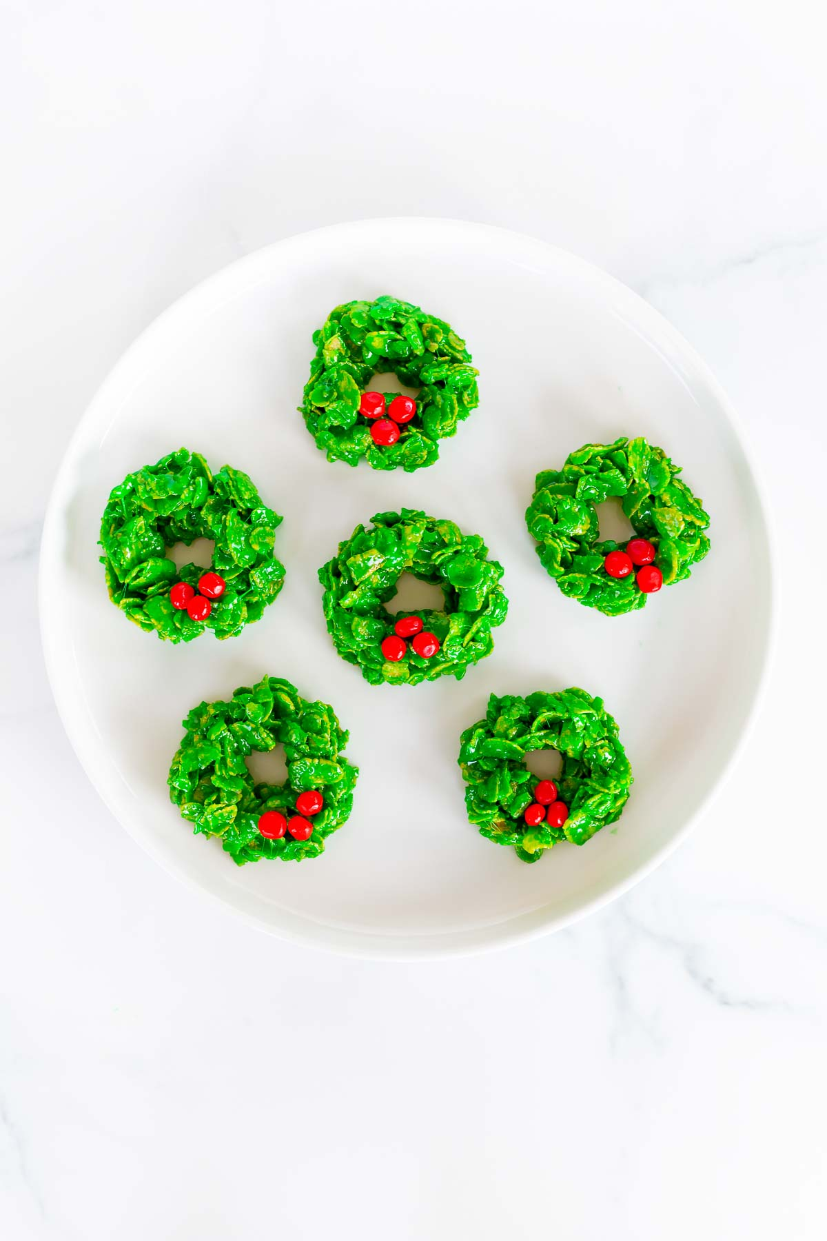 christmas wreath cookies on white plate