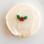 A single white frosted round Christmas Sugar cookie on a marble surface, single holly berry decoration in center.