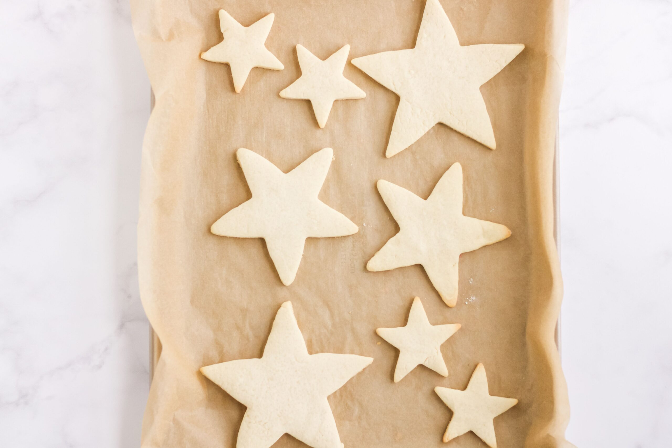 Baked cut out sugar cookies in a star shape on a parchment lined baking sheet.