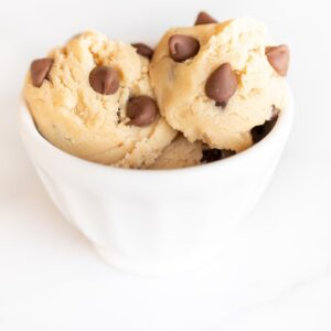 A white bowl on a white surface with scoops of an edible cookie dough recipe with chocolate chips.