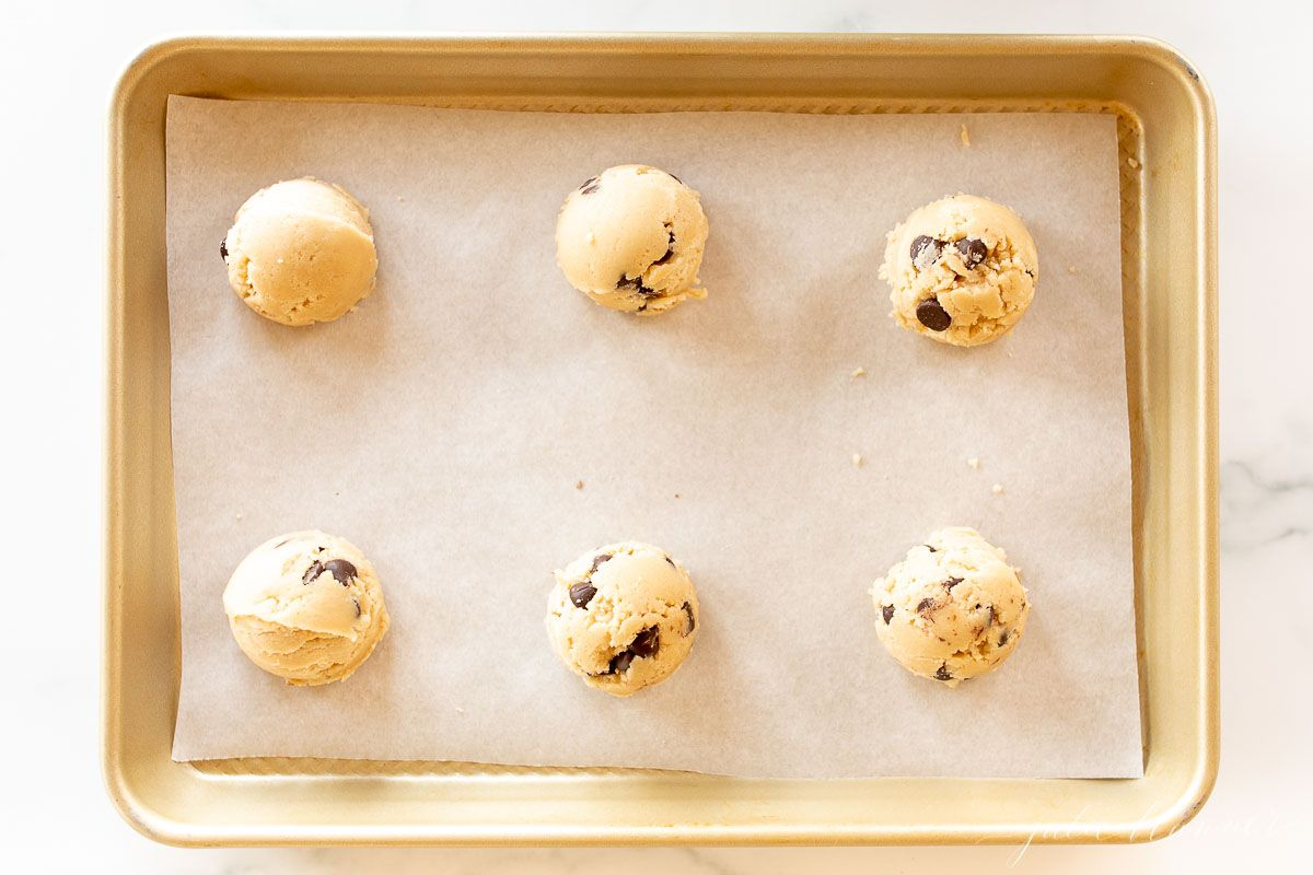 A gold cookie sheet, lined with parchment paper, topped with six balls of edible cookie dough.
