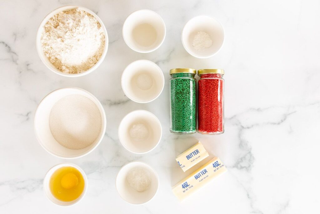 A marble surface with small white bowls fills with ingredients for funfetti cookies.