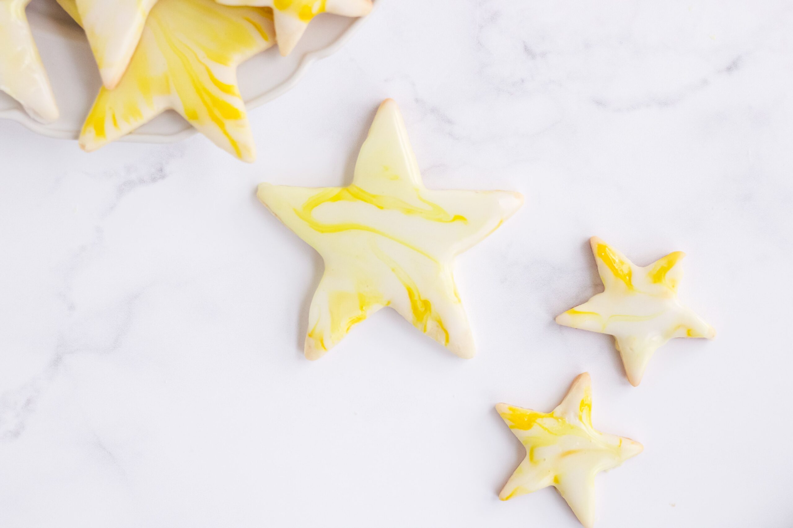A marble surface topped with star shaped sugar cookies with a yellow and white marbled icing.