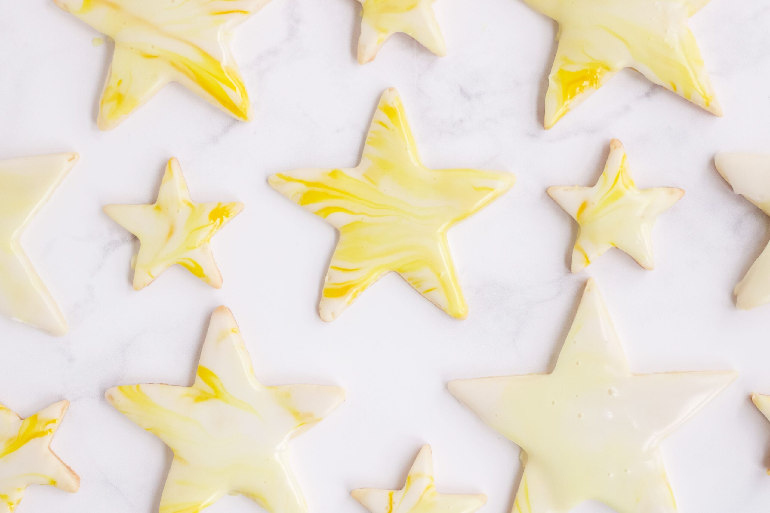 A plate of star shaped sugar cookies topped with marble icing.