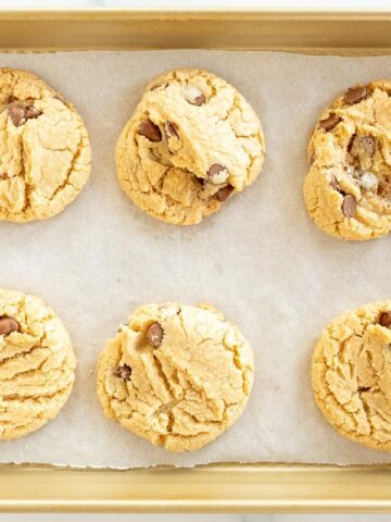 Six marshmallow cookies with chocolate chips on a gold baking sheet lined with parchment paper.