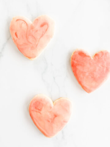 3 heart shaped sugar cookies on marble surface