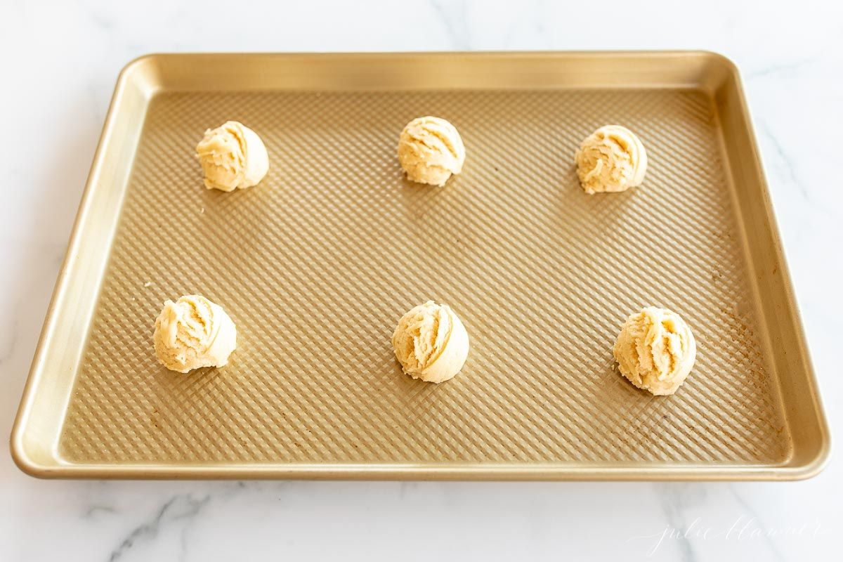 Lemon cookie dough balls on a gold baking sheet.