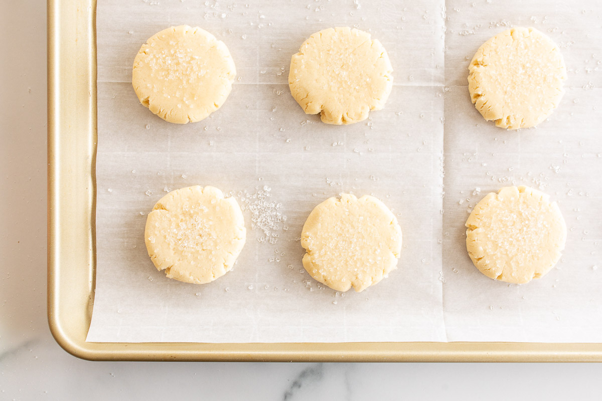 pressed sugar cookies on parchment lined baking sheet