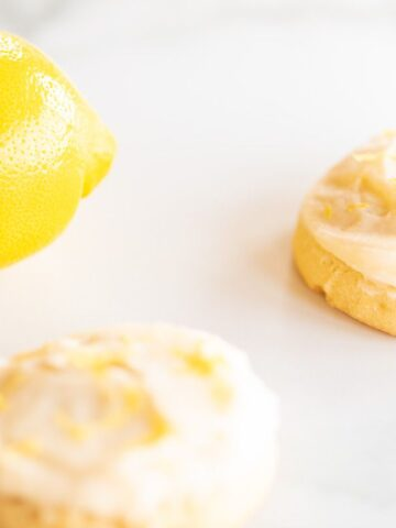Frosted lemon cookies on a marble surface, whole lemon in the background