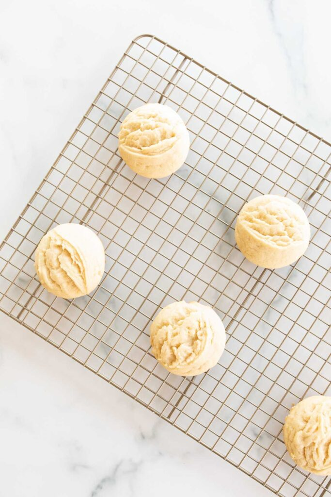 Small lemon cookies on a wire cooling rack on a marble countertop.