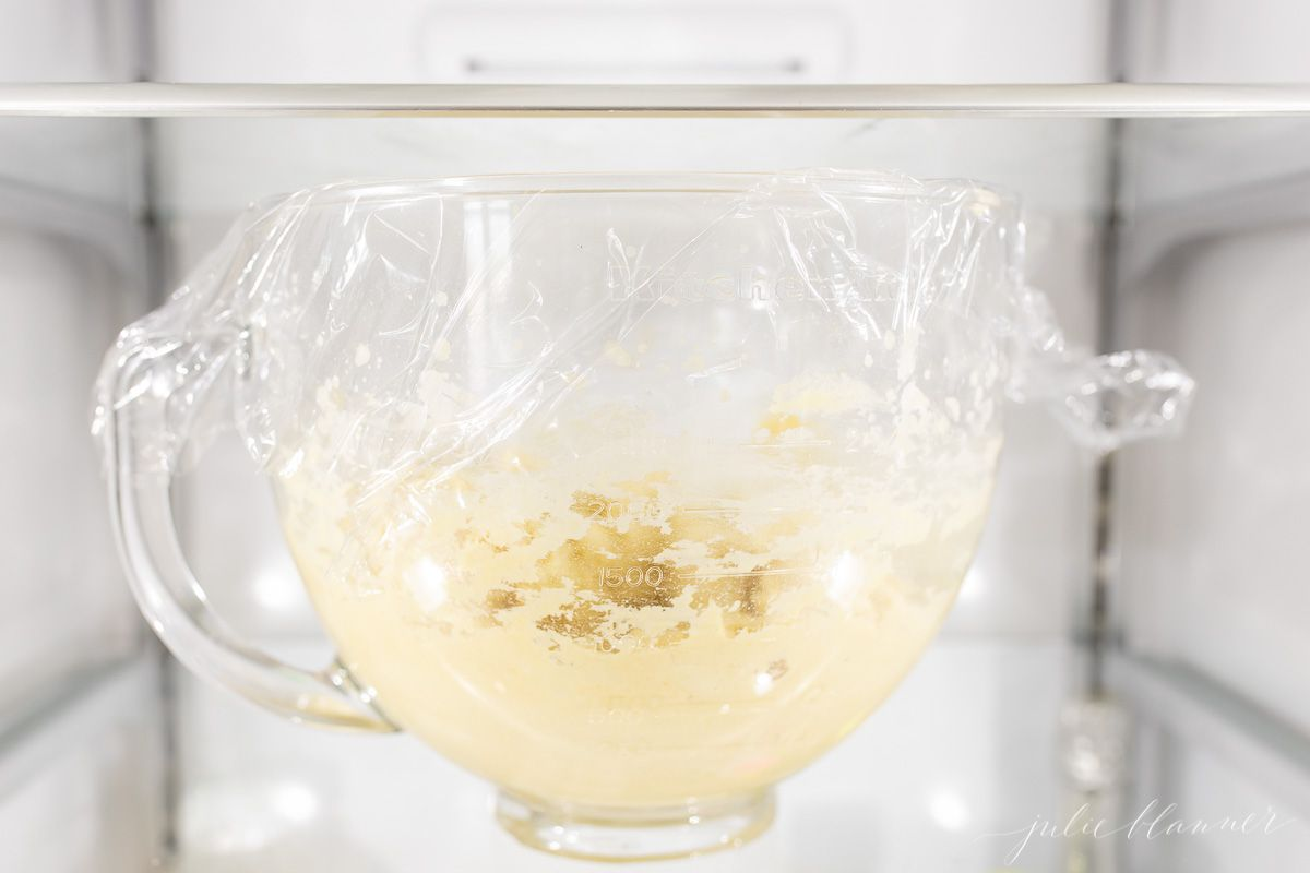 A clear mixing bowl wrapped in plastic, full of cookie dough in a refrigerator.