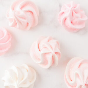 pink and cream meringues on marble surface
