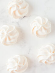 Pale pink and white meringues on a marble surface.