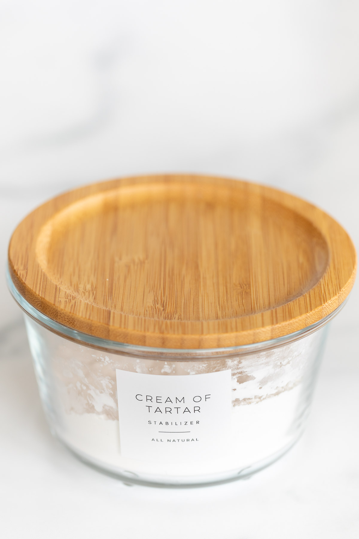 cream of tartar in glass container with wood lid and label