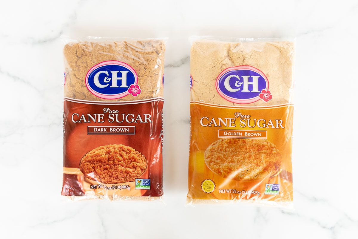 A marble countertop with two unopened bags of brown sugar - dark brown sugar on the left and light brown sugar on the right for a comparison.