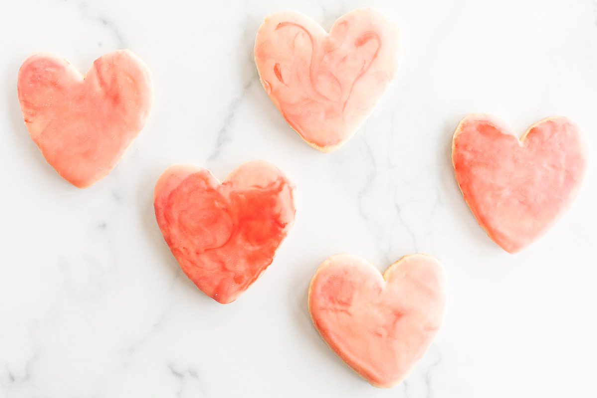 Sugar cookies in a cutout heart shape place on a marble surface, topped with pink royal icing.