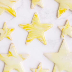 Star shaped cutout sugar cookies topped with yellow marbled royal icing, spread out on a marble surface.
