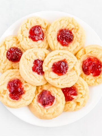A white plate filled with strawberry cheesecake cookies.