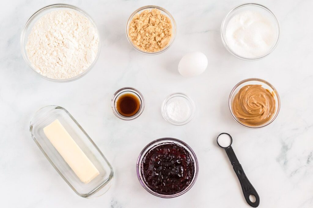 Ingredients for pb&j cookies on a white marble surface.