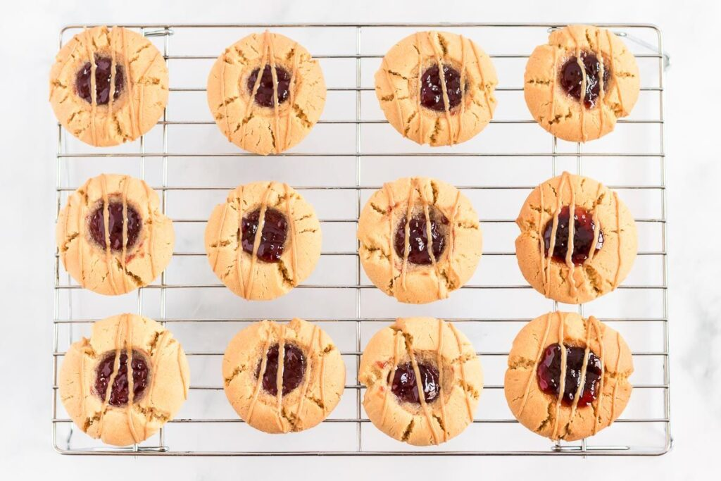 Peanut butter and jelly cookies laid out on a wire cookie cooling rack.