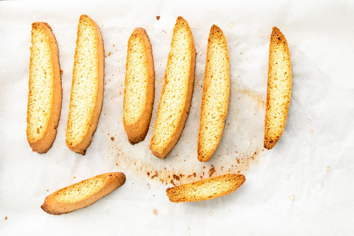 Vanilla biscotti laid out on a white surface.