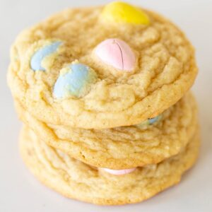 A stack of multiple mini egg cookies, on a marble surface for Easter.