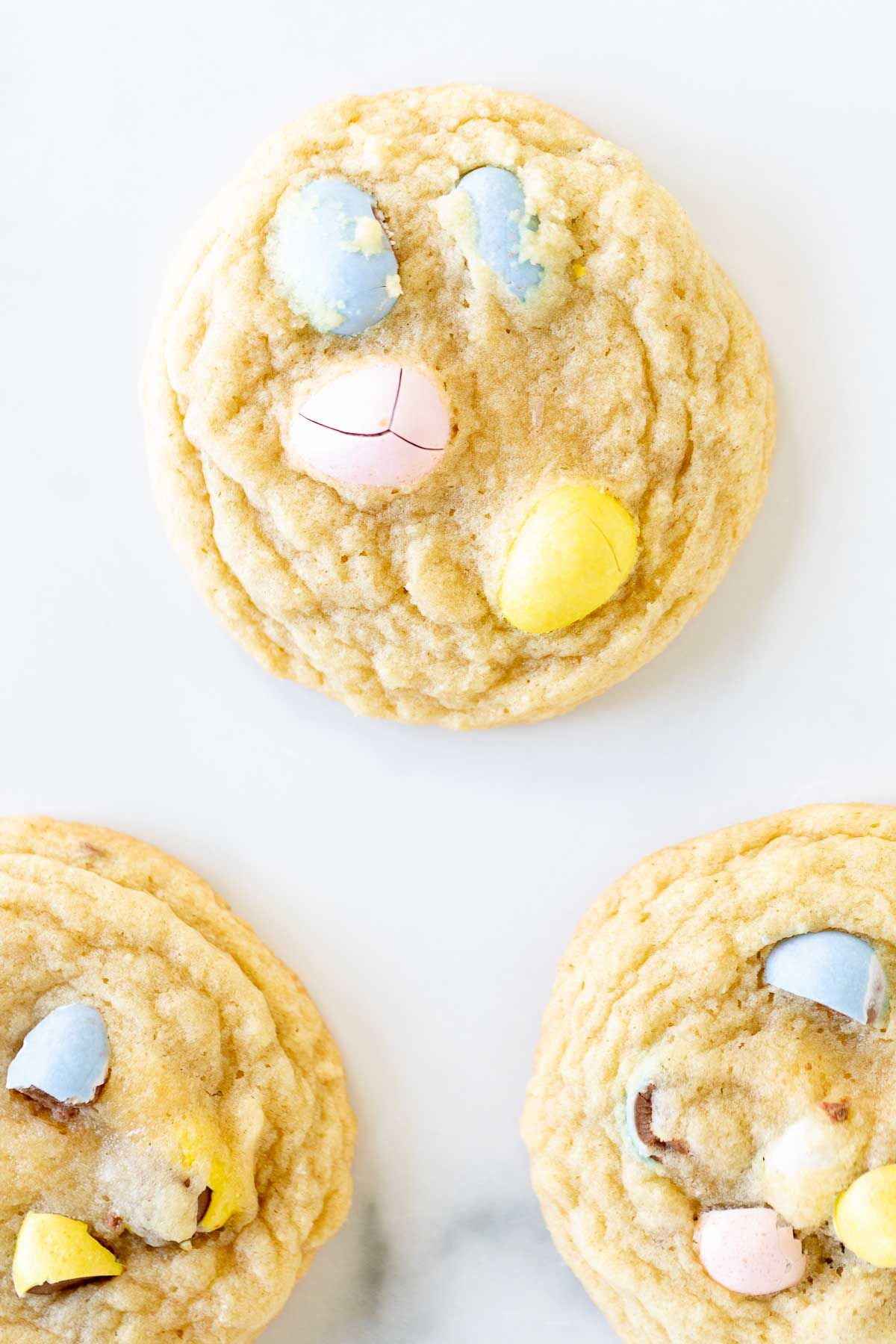 Mini egg cookies with pastel colored candy eggs spread out on a marble surface.