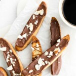 Vanilla biscotti covered in chocolate on a marble surface, bowl of chocolate chips and cup of coffee in the background.