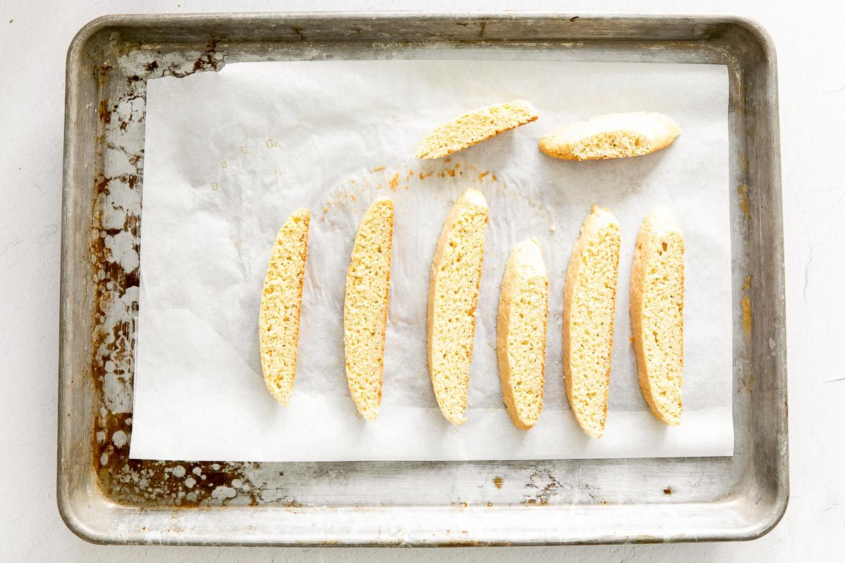 Vanilla biscotti cookies laid out on a parchment paper lined baking sheet.