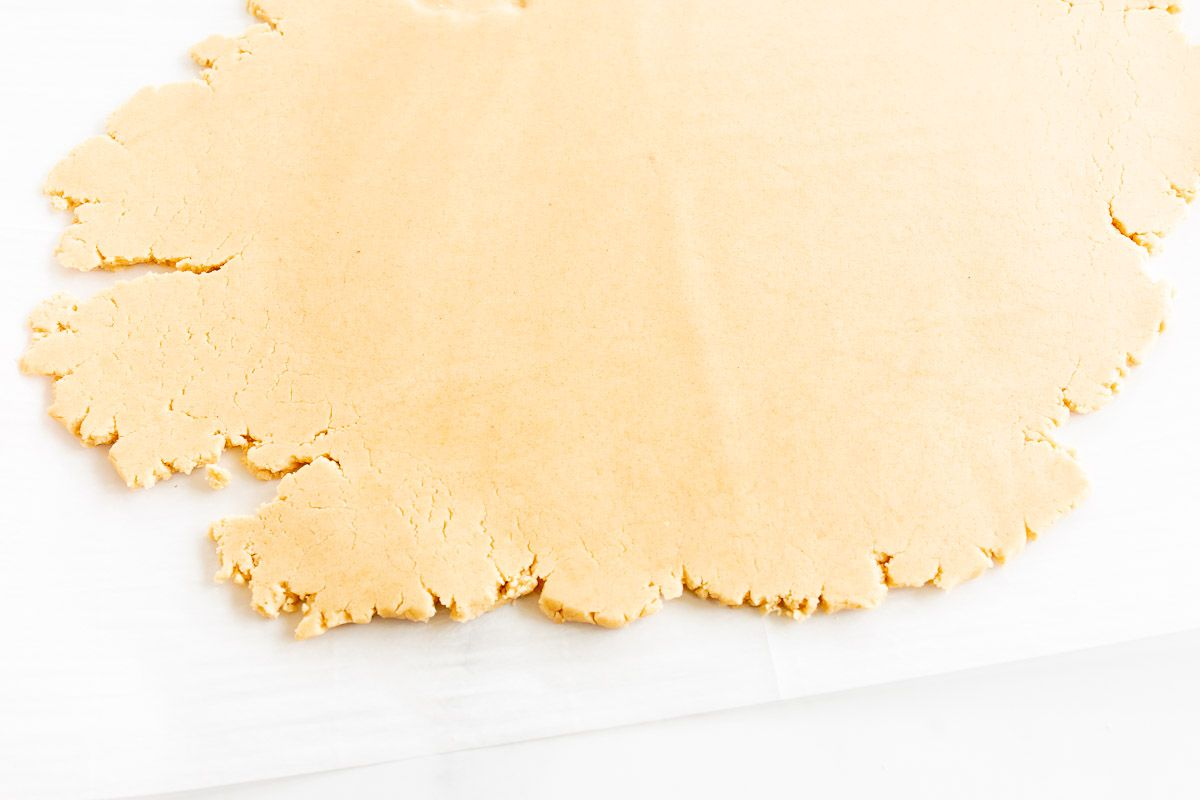 A flat chunk of peanut butter shortbread cookie dough on a sheet of parchment.