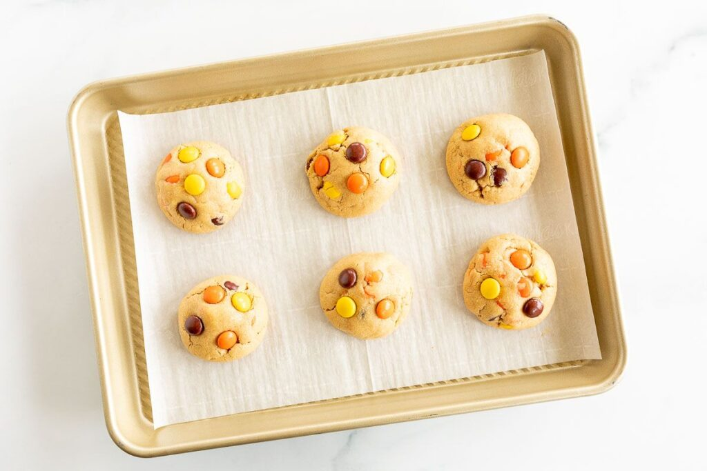 baked reeses pieces cookies on a cookie sheet lined with parchment paper