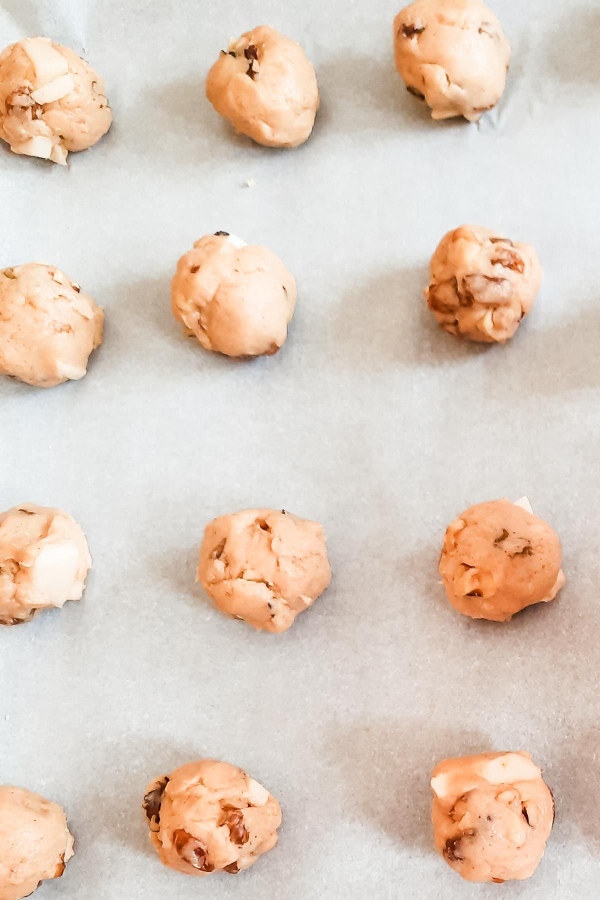 Apple cookie dough scoops on parchment paper.