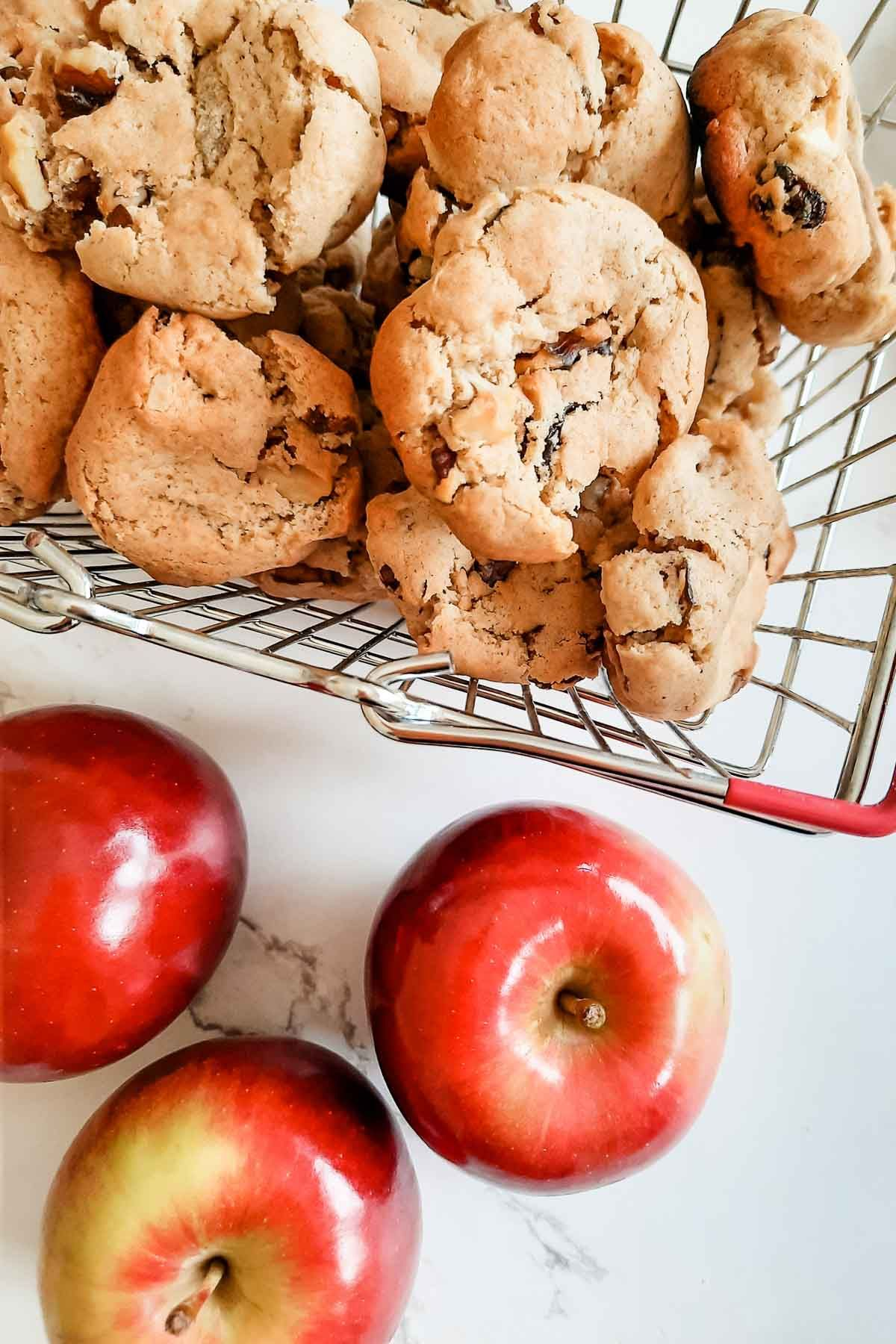 Apple raisin softies in a metal basket with apples nearby.