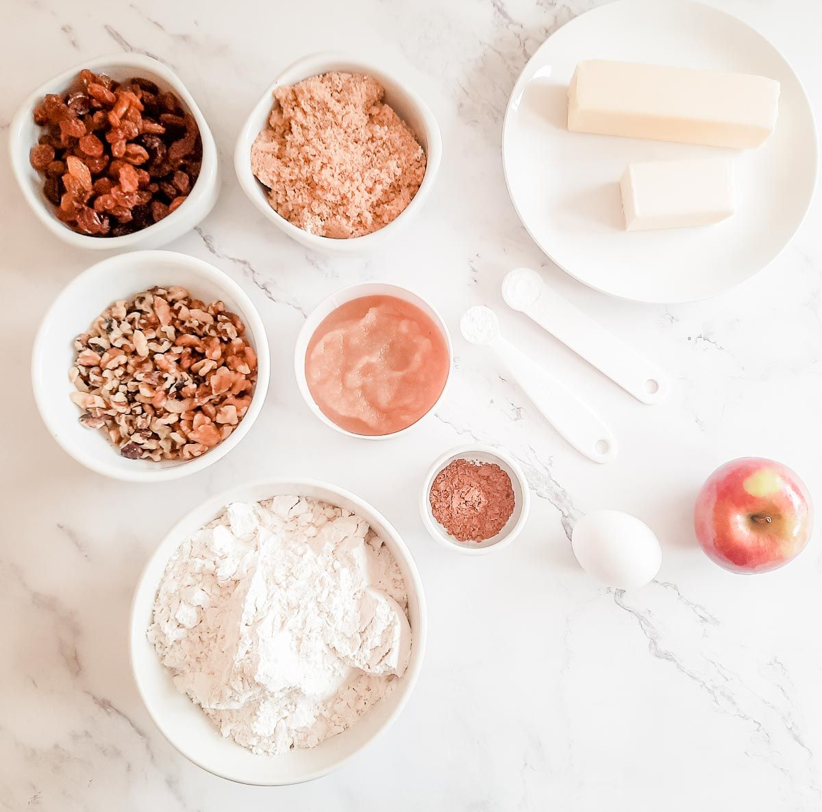 Cookie dough ingredients laid out in white bowls on a marble surface.