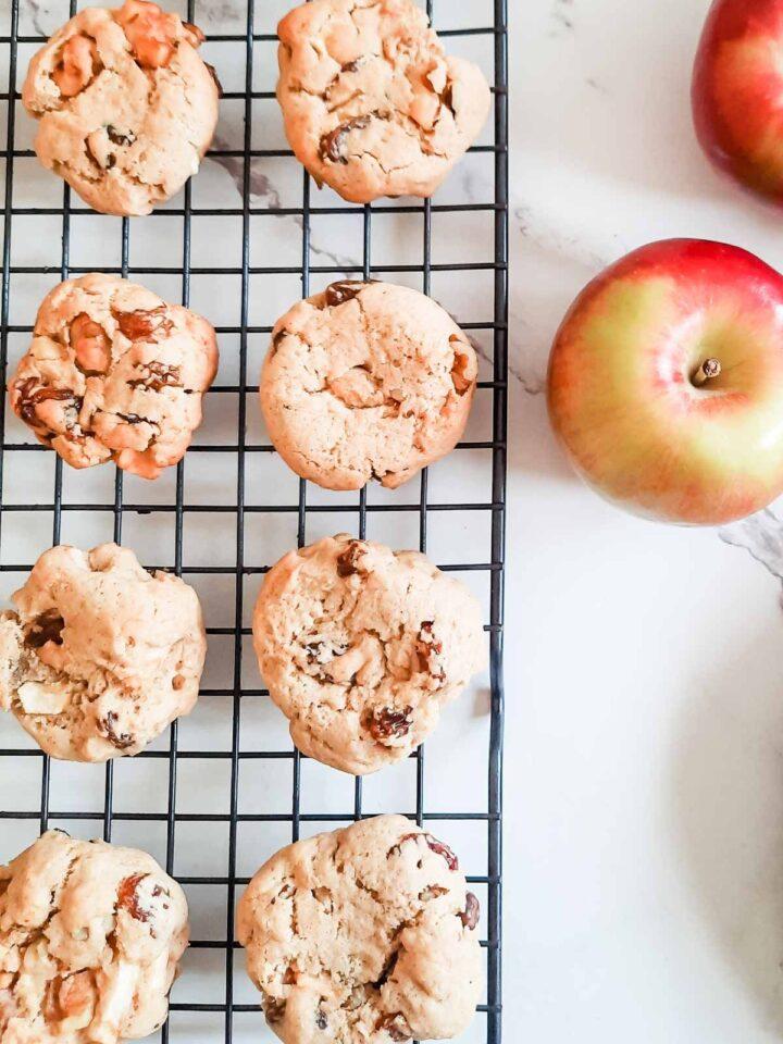 Apple raisin softie cookies on a baking sheet, apples nearby.