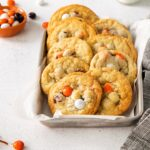 Halloween cookies with M&Ms in a small silver tray lined with parchment. Gray towel to the side.